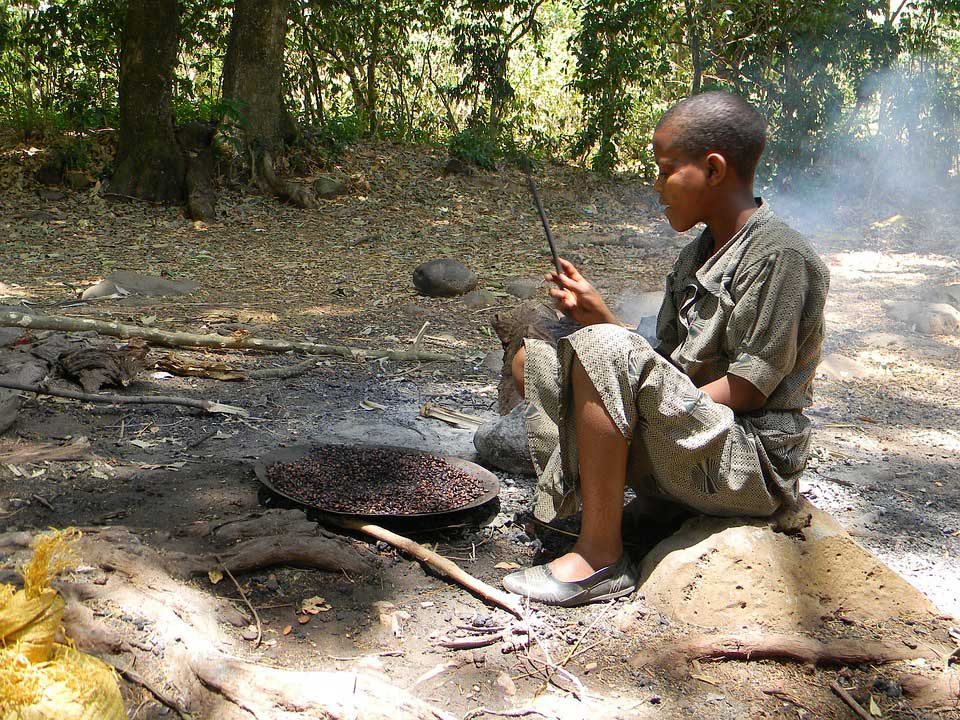Kind in Äthiopien röstet Kaffee