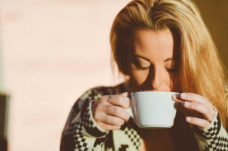 Frau trinkt Kaffee und genießt Aroma